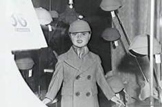 A window display ishowing the price tag and number of coupons required for the purchase of a child's overcoat and caps