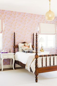 Little girl's room with gold pendant light and patterned wallpaper