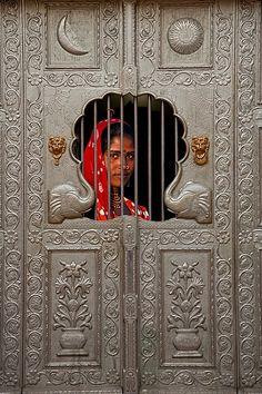 Gypsy girl behind a door, Pushkar, Rajasthan, India.