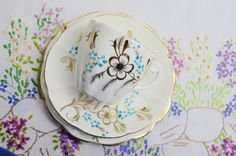 pretty scalloped china trios in cream gold and blue  with a lovely cream/ivory base and gold floral details and a punch of blue, these are very pretty  cup diameter 7 1/2cm h 6 1/2cm  saucer 14cm diameter  side plate 15 1/2cm diameter  some slight loss of gilding but otherwise in good vintage condition  please visit us on facebook at tillyandarthur so you can keep up to date with our latest news and offers.