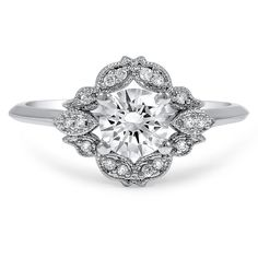 This breathtaking engagement ring showcases a round brilliant diamond surrounded by an ornate halo of diamond accents. A petite knife edge band adds to the vintage look of this piece.