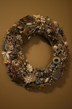 Foam wreath form wrapped in fabric, with my grandma's old jewelry sewn on.  Great use for broken pieces and earrings missing a mate!