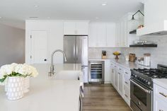Large kitchen island topped with white quartz countertops is fitted with an apron farmhouse sink and a satin nickel gooseneck faucet facing a stainless steel oven range flanked by white shaker cabinets adorning brushed brass pulls and finished with an under cabinet glass door mini wine cooler and double door stainless steel refrigerator.