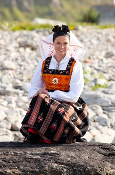 "The Vigra bunad worn with the red stockings and red embroidery on the head kerchief signals this woman is not married. In Norway this is called ""jenteskaut"" and it is worn with several of the bunads from Sunnmøre"