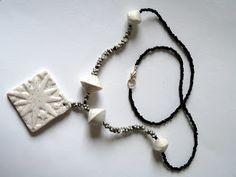 Collier avec une perle carré à relief couleur blanc pailleté comme pendentif et des petites perles grises et noires