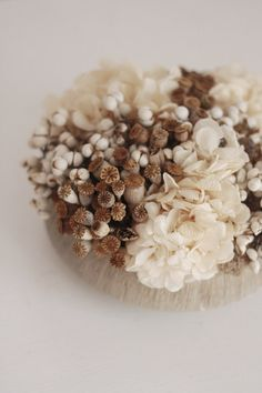 ESTY: soft textures - modern dried flower arrangement a low design mixed with small poppy pods, white tallow berries and soft creamy white preserved hydrangea blooms tucked into a low cement bowl with a