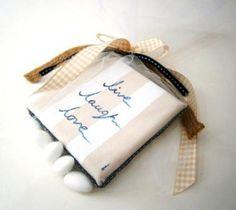 """Καδράκι – μπομπονιέρα για βάφτιση αγοριού, ριγέ μπεζ λευκό με navy blue γράμματα, που αναγράφει """"live-laugh-love"""". Κάθε καδράκι είναι μοναδικό και ζωγραφίζεται ένα ένα στο χέρι. Τοποθετείται σε πουγκί τούλινο μαζί με 5 μεγάλα κουφέτα και δένεται με ασορτί κορδέλες. Στο συγκεκριμένο θέμα μπορούν να διαμορφωθούν αντίστοιχα και το κουτί βάφτισης, η λαμπάδα, το λαδόκουτο, το σετ λαδικων, το κουτί μαρτυρικών, το βιβλίο ευχών, τα μαρτυρικά, ο στολισμός κολυμπήθρας καθώς και τα παιδικά δωράκια…"""