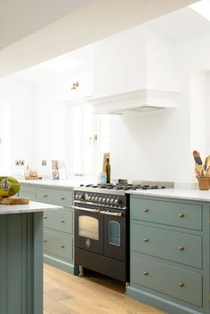 This stylish black Bertazzoni range cooker looks so chic with our simple Shaker cabinets painted our new 'Trinity Blue' colour