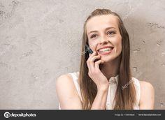Скачайте стоковую фотографию Красивая улыбается молодая женщина, говорить на смартфоне и глядя в сторону - 153978826 из многомилионной коллекции лицензионных фотографий, иллюстраций и векторных изображений Depositphotos.