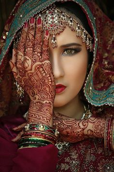 A beautiful woman covered in native garb and Henna art