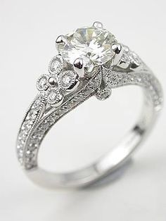 Dramatic Diamond Engagement Ring, RG-2817m, A floral and diamond design on the shoulders  enhances this 18k white gold antique style engagement ring. In total, seventy-four round brilliant cut diamonds totaling 0.50 carats adorn the band. Eight of these diamonds, four on each side, are arranged in the floral design. The diamond flowers flank a 1.12 carat GIA certified round brilliant cut diamond at the center. This diamond is J in color and has a clarity of SI2.  This is a new engagement…