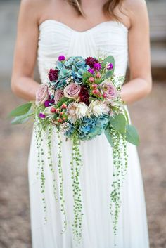 Petal Pusher used roses, hydrangeas, dahlias, 'Blushing Bride' proteas, scabiosas, berries, and string of pearls to create this beautifully eclectic bouquet. | Photo by Kasey and Ben Photography