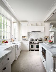 Carrara marble was used for the counters as well as the backsplash above the Wolf range; the pot filler and sink fittings are by Waterworks | archdigest.com