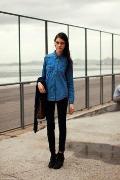Девушка в черных джинсах и джинсовой длинной рубашке рубашке
