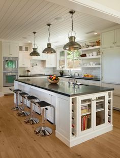 White kitchen cabinets, white paneled wood ceiling and trim, light wood floors. East Mountain home, Santa Barbara. NMA Architects and D. D. Ford Construction.