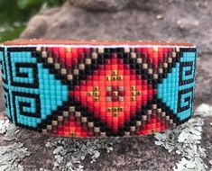 Items similar to Beaded Spiral Design Bracelet in Reds, Golds, Black and Brown on a Torquiose Background. Hand Made by the Artist on Etsy Loom Bracelet Patterns, Seed Bead Patterns, Bracelet Designs, Beading Patterns, Beading Ideas, Beading Projects, Native American Patterns, Native American Beadwork, Kilt Pattern