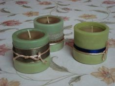 Hand poured candles in green coloured cylindrical wax shells decorated in shades of gold