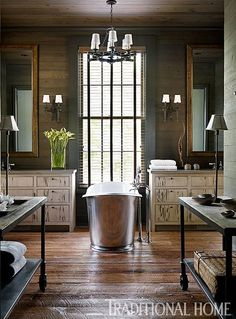 Centered between twin vanities, and bathed in natural light, is a lovely soaking tub. - Traditional Home ® / Photo: Emily Jenkins Followill / Design: Susan Ferrier