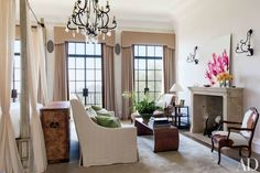 In the master bedroom of Gisele Bündchen and Tom Brady's former California home, the chandelier and the sconces above the mantel are by Gregorius/Pineo; a Joan Behnke–designed sofa clad in a Loro Piana linen faces a Dennis & Leen low table, and the custom-made rug is by Tai Ping.