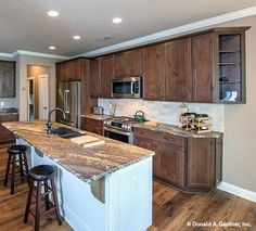 Rustic cabinets and flooring complete this island #kitchen. The Butler Ridge #1320-D. http://www.dongardner.com/house-plan/1320-D/the-butler-ridge. #IslandKitchen #DreamHome