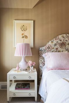 Pink and beige bedroom features paneled walls framing pink and gray floral headboard on full bed dressed in white bedding and pink ruffled shams beside framed floral print over 2 drawer nightstands adorned with ring pulls topped with pink table lamp with pink pleated shade.