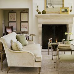 Elegant European inspired living room with limestone fireplace, cream sofa, and patina style from Giannetti Home and Brooke Giannetti.