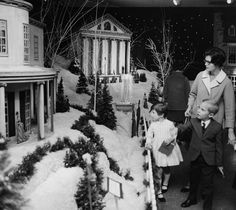 Thalhimers Christmas exhibit, located in the 6th floor auditorium; the exhibit features scale models of notable Richmond landmarks at Christmas time (in the snow); the rear of the Wickham House and the Virginia State Capitol are visible in the image; the O'Keefe family (Mrs. Charles O'Keefe, Joan and Chuck of Midlothian, Virginia) view the Wickham House. - December 17, 1968  | Richmond Newspapers, Inc; Bill Lane