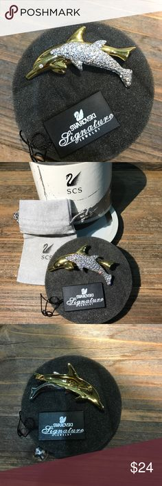 Swarovski fine jewelry Dual dolphins in gold metal with brilliant crystals. This pin is in perfect condition with original packaging. Lovely accessory in a timeless design.  Priced to sell. No trades, please. Swarovski Jewelry Brooches