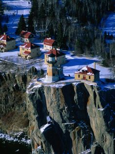 Lighthouse and Houses Under Blanket of Snow on Top of Cliff at Split Rock, Minnesota, USA