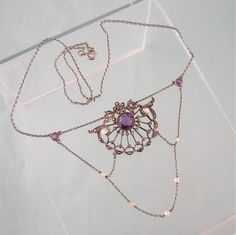 This necklace is a beautiful example of Edwardian sterling jewelry. A slightly domed, openwork medallion features a large round amethyst center stone