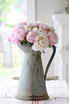 Romantic arrangement of pink and white peonies in a vintage pitcher