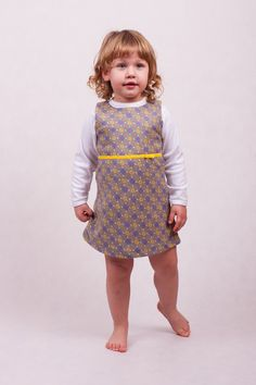 Dress without sleeves. Sweet pattern with little yellow and violet flowers, delicate ribbon at the front. Zip fastening at back.