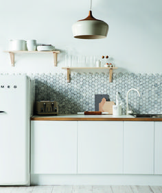 Marble Polygon hex kitchen tiles with white cabinets and wood / white countertops. You don't normally see hex staggered at the top, typically there are cabinets containing it or molding.