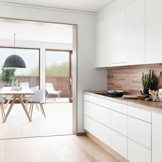 Kuchyň ve skandinávském stylu v provedení bílá - světlé dřevo. Jídelna: židle About a Chair, lampa Under the Bell, stůl Split, Muuto