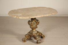 Balaustro intagliato e dorato a reggere piano in marmo sagomato.