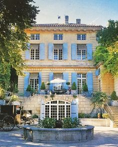 (John Yunis)  Lillian and Ted Williams in Provence, Pavilion de Bidaine, Part 8: Exterior. I believe this is the entrance facade, but not sure. Classic pale blue shutters against the limestone facade.  In the foreground is one of several fountains that surround the folie. The 18th century carriage is also from the collection of Mrs. Williams.  From World of Interiors, photo by Michael Mundy  #18thcentury #17thcentury #france #paris #provence #chateau #library #maisondeplaisance #estate…