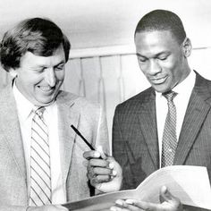 Michael Jordan looks over his rookie contract with then-Bulls general manager Rod Thorn, the man who drafted him No. 3 overall.