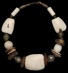 19th c. shank shell Mauritania, white glass European, silver beads Tibet and Yemen, Sassanian (300 AD) camel bone spindle whorls. contemporary copal Africa, and New Guinea shell currencies.