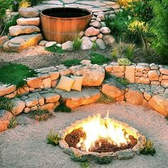 Backyard campfire  A built-in firepit is the hub of gatherings in this garden. Sandstone cobbles edge the 5-foot-diameter lava rock–topped pit, which blazes with gas-fed flames. A sandstone wall, scattered with cushions for comfort, serves as seating. Thyme and other herbs grow around the firepit and between the seat wall's stones. Photo: Holly Lepere, Sunset.com