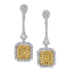 Two Radiant Cut Fancy Yellow Diamonds Totaling 1 51 Ctw Sit Framed By Rows Of Gold Diamond Earringsgemstone Earringsdangle