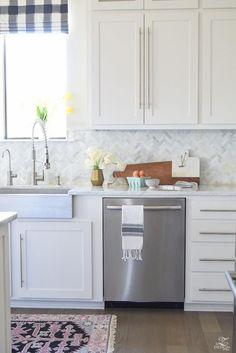 White Cabinet, counter, wood floor, Herringbone marble backsplash!