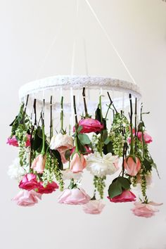 For a whimsical decoration, hang three dozen flowers with ribbons from a delicate lace-covered embroidery hoop to make a flower chandelier.