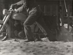 Mario Finocchiaro. Man holding up Motorcycle , c. 1970s.