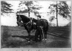 [O.H. Hart, full-length portrait, standing, left profile, in uniform, alongside horse]