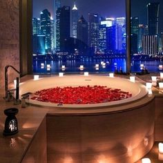 bath with red roses and candles and a beautiful view of the city