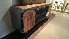 """Weight in What The Inspiration for this Piece Was. A submarine, wood stove, a train? This buffet was made from solid pieces of mango and iron. Recently made and imported from India, this piece has two small enclosed cabinets and one main cabinet with slots opening to the back for entertainment units. 30"""" 78"""" W -$1195"""