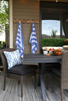 Outdoor dining space with brown wicker and wood dining table, blue and white striped towels, blue and white trellis pillow and blue, brown and gray outdoor rug. Love this video tour of this stunning backyard entertaining space! Outdoor Rooms, Outdoor Dining, Outdoor Furniture Sets, Outdoor Decor, Furniture Ideas, Dining Table, Dining Area, Outdoor Ideas, White Trellis