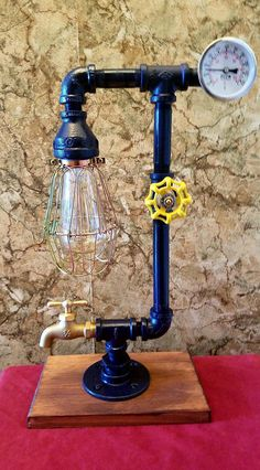 """This industrial lamp adds the perfect touch to any environment. The vintage lighting offers the right amount of glow allowing you to sit in relaxation. Hand Made in the USA. This industrial lamp is made with 1/2"""" steel pipe and fittings. M Mounted on a beautiful pine board . Includes a 40"""