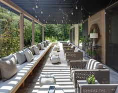 extra large patio with black painted pergola and dangled hang lighting fixtures full length couches with accent pillows rounded center tables in white of Turn Your Backyard into Inviting Spot just with These Pergola Designs for Patio