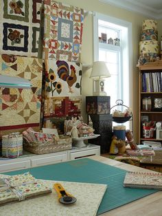 Wonderful sewing room. I like the rods for displaying the quilts.